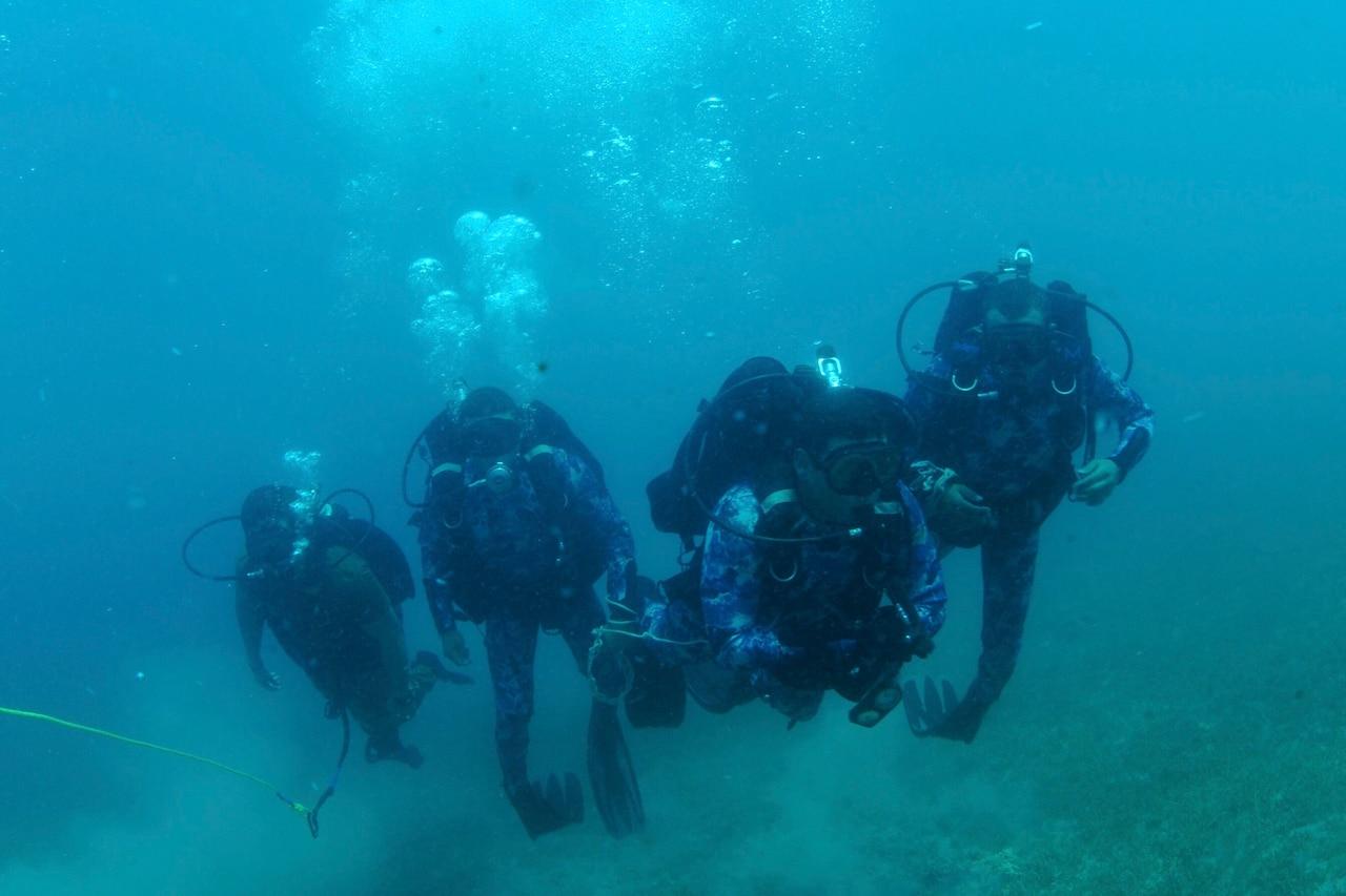 Four sailors swim underwater in scuba diving gear.