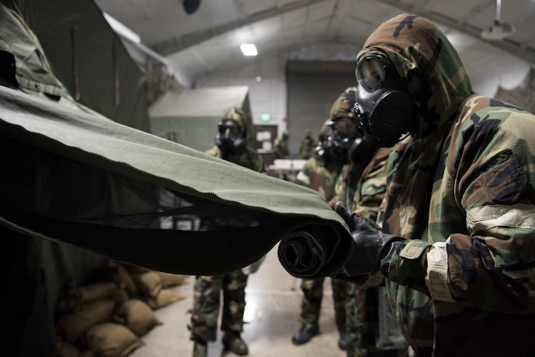 A group of U.S. Air Force Airmen roll up a tent door during a newly-implemented chemical, biological, radiological and nuclear defense training course exercise at Joint Base Elmendorf-Richardson, Alaska, Jan. 8, 2019. One of the key changes made embraces the reintegration of hands-on, in-person instruction, and reduces computer based training, allowing Airmen to receive a more tailored learning experience. (U.S. Air Force photo by Airman 1st Class Crystal A. Jenkins)