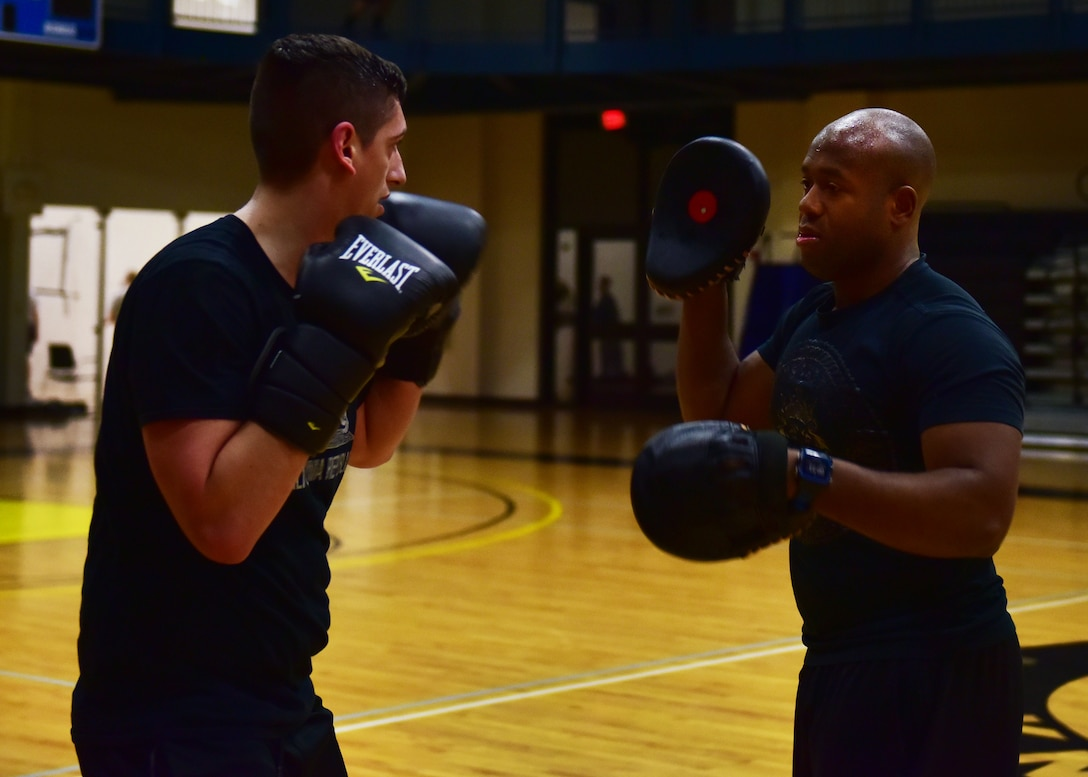 Two men wear boxing equipment practice boxing.