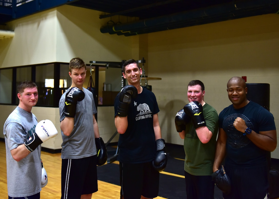 Five men in different workout clothes hold up their boxing gloves and smile at the camera.