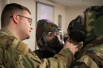 U.S. Air Force Senior Airman Richard Blackburn, 773d CES Emergency Management chemical, biological, radiological and nuclear (CBRN) instructor shows Tech. Sgt. Kasama Slaton, 673d Medical Operations Squadron, how to identify exposures risks to Senior Airman Kolbe Kleinschnitz, 3rd Maintenance Squadron, during a newly-implemented CBRN defense training course at Joint Base Elmendorf-Richardson, Alaska, Jan. 8, 2019. One of the key changes made embraces the reintegration of hands-on, in-person instruction, and reduces computer based training, allowing Airmen to receive a more tailored learning experience. (U.S. Air Force photo by Airman 1st Class Crystal A. Jenkins)