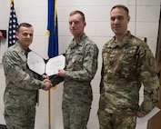 U.S. Brigadier General Darrin Slaten, commander of the 176th Wing, Alaska Air National Guard, joined by U.S. Army Sgt. 1st Class Shawn Landon, presents U.S. Air Force Airman 1st Class Daniel Randolph The Alaska Humanitarian Service Medal during a ceremony at Joint Base Elmendorf-Richardson, Alaska Jan. 9, 2019. Randolph was awarded the medal for exceptional response after witnessing a para-gliding accident on March 10, 2018 while hiking. Randolph assumed personal risk to reach the pilot by climbing an ice laden cliff and provided immediate aid by fashioning a sling, he was also able to grab the pilot's gear, guide the pilot down the cliff as well as the Butte Trail.