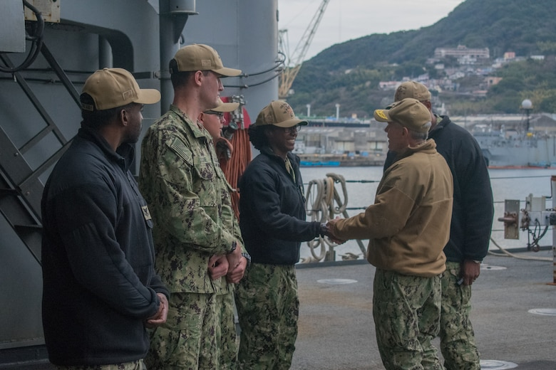 SASEBO, Japan (Jan. 9, 2019) Vice Adm. Phil Sawyer, the U.S. 7th Fleet commander, presents a coin to Culinary Specialist 3rd Class Latia Gill, assigned to the amphibious dock landing ship USS Ashland (LSD 48), during a waterfront visit to forward deployed naval forces operating out of Fleet Activities Sasebo, Japan.