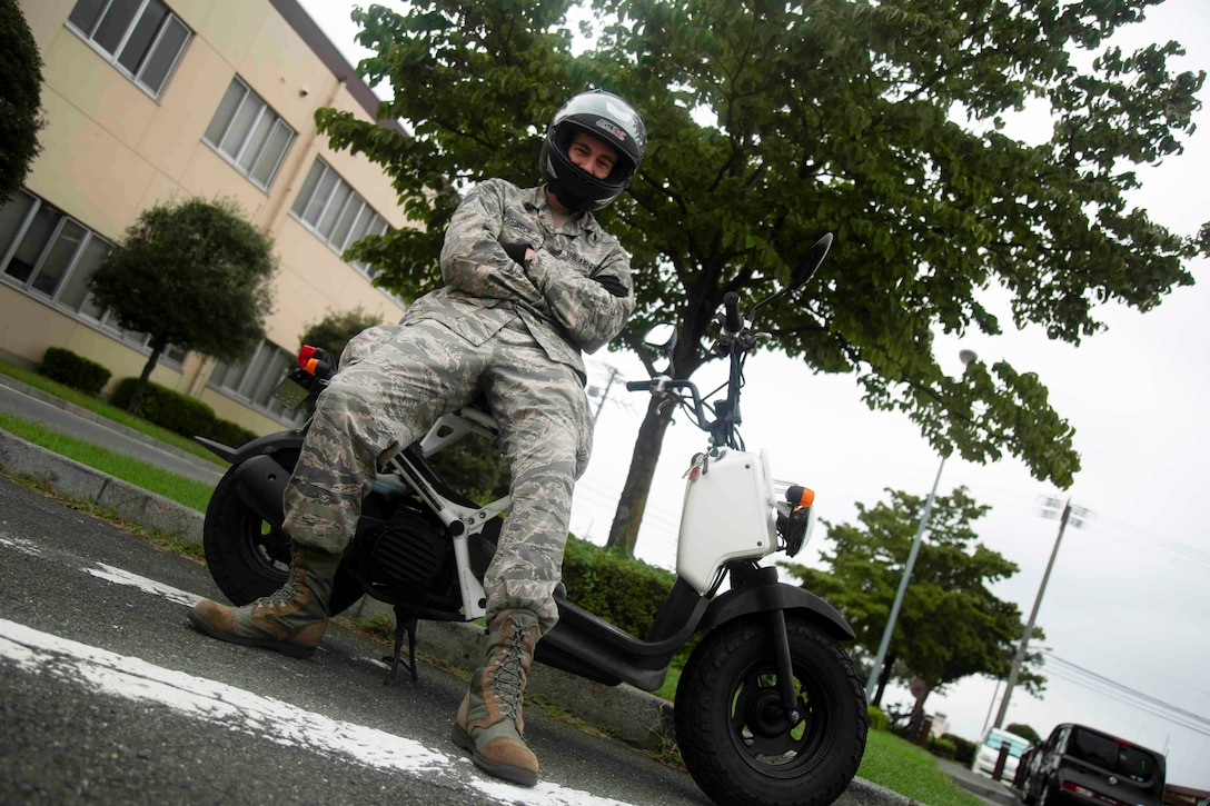 Staff Sgt. Kyle Johnson, photojournalist with the 374th Airlift Wing Public Affairs office poses on his scooter, August 29, 2018. Johnson crashed at low speed a month later resulting in an extended hospital stay. (U.S. Air Force photo by Senior Airman Dustin Payne)