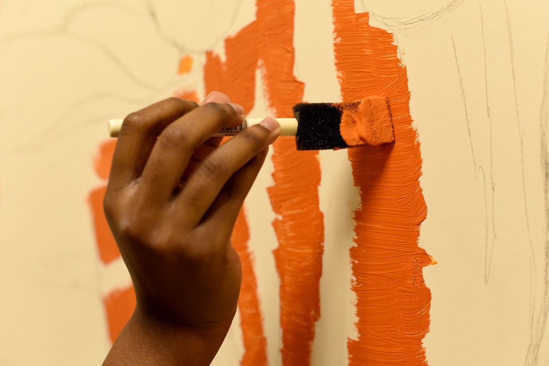Volunteer Nadja Ellis paints a tiger for a mural in the 100th Communications Squadron building at RAF Mildenhall, England, Dec. 20, 2018.  The tiger is part of a children's picture book-themed mural covering the walls of the Mothers' Room, or lactation room, in the squadron.  (U.S. Air Force photo by Senior Airman Lexie West)