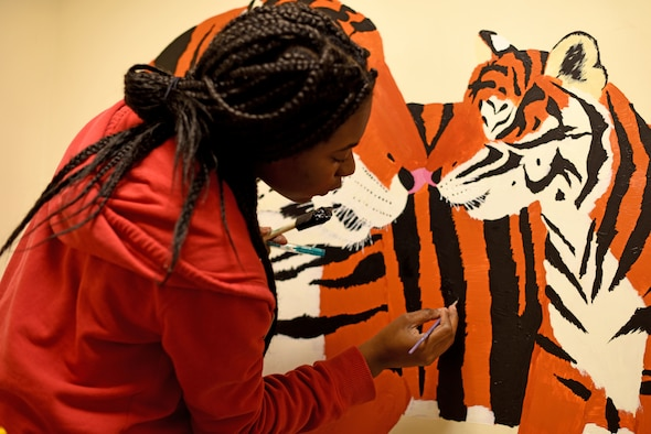 Volunteer Nadja Ellis paints tiger stripes for a mural in the 100th Communications Squadron building at RAF Mildenhall, England, Dec. 20, 2018. Ellis painted the mural to cover the walls of the Mothers' Room and create a tranquil space for new mothers to breastfeed.  (U.S. Air Force photo by Senior Airman Lexie West)