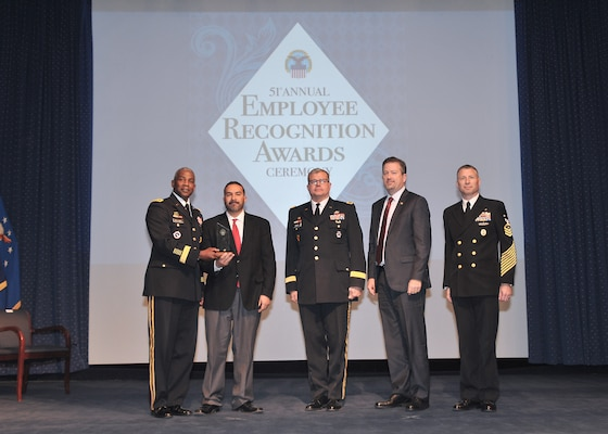 DLA Director Army Lt. Gen. Darrell Williams, left, DLA Troop Support Commander Army Brig. Gen. Mark Simerly, center, and Navy Command Master Chief Shaun Brahmsteadt (far right) present Roberto Santana Irizarry, second left, contracting officer representative, DLA Troop Support Subsistence supply chain, with the DLA Leader of the Year award during the 51st Annual Employee Recognition Awards Ceremony, Dec. 13, 2018 at the McNamara Headquarters Complex Auditorium, Ft. Belvoir, Va. Santana Irizarry received the award for his significant achievements in providing logistical support to the Warfighter throughout Afghanistan.