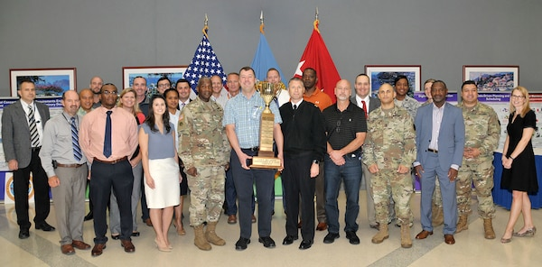 Participants who helped DLA win the 2018 Commander's Cup pose with DLA Director Army Lt. Gen. Darrell Williams (front row, fourth from left) and Navy Command Master Chief Shaun Brahmsteadt (front row, sixth from left), DLA senior enlisted leader. Holding the trophy is Andy Green of DLA Strategic Materials, who organized DLA's participation in the events throughout the year.