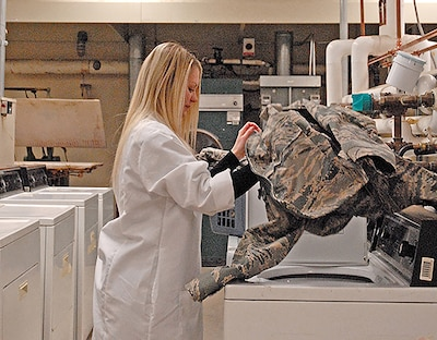 Product Test Center-Analytical scientist Nicole Dysart washes an Air Force jacket. Specifications the lab tests for include maintaining certain qualities after multiple washes, so the scientists often do laundry at work.