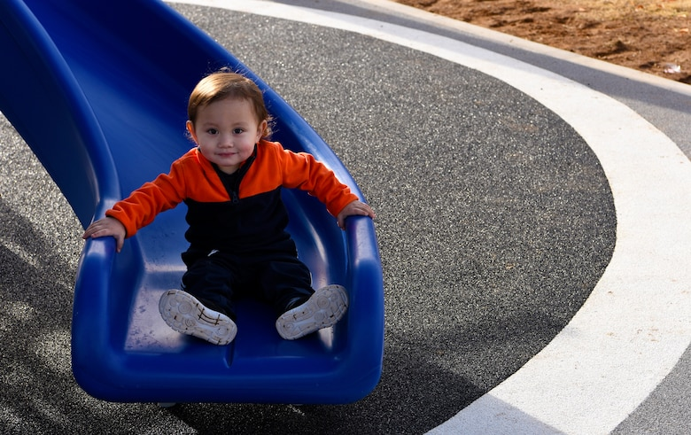A young Thunderbolt smiles after riding down a slide at the new Fowler Park playground, Jan. 9, 2019, at Luke Air Force Base, Ariz.