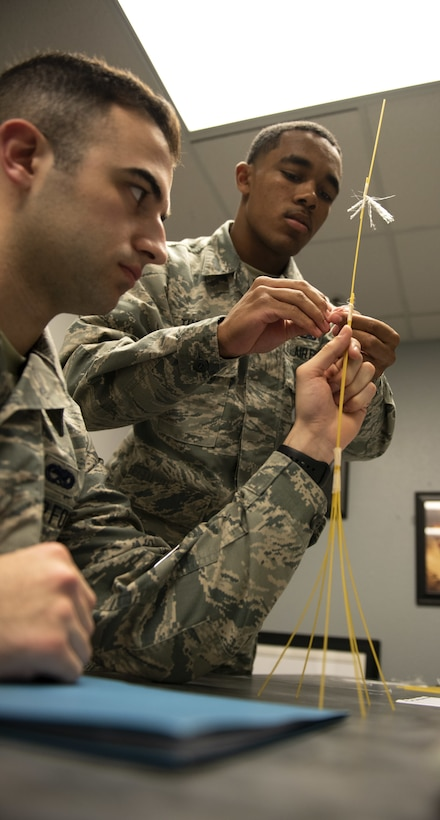 Airman 1st Class Resean Thomas, 60th Aircraft Maintenance Squadron C5 communications navigation apprentice, right, works with Airman 1st Class Mike Sobeck, 60th MXS C5 crewchief, during a competition with the First Term Airman Course class Jan. 10, 2019, at Travis Air Force Base, Calif. Airmen attend FTAC to help transition from the technical training atmosphere to the operational Air Force. (U.S. Air Force photo by Airman 1st Class Jonathon Carnell)