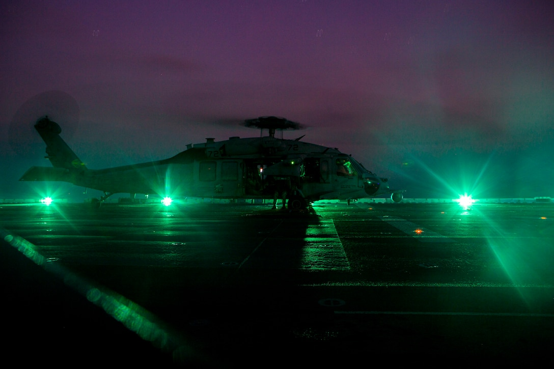 A helicopter at night parked on the ground.