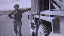 Black and white photo with soldier leaning up against a old Army truck.
