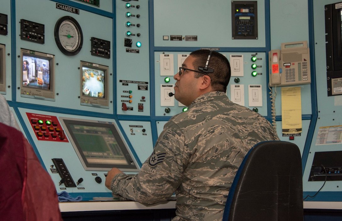Staff Sgt. Corona Guerarzo, 60th Medical Group Hyperbaric Medicine Flight technician, monitors patients receiving hyperbaric oxygen therapy treatment, Dec. 8, 2019, at David Grant USAF Medical Center, Travis Air Force Base, California. The hyperbaric oxygen treatment chamber uses state-of-the-art technology to aid patients who are in need of therapy for a multitude of diagnosed illnesses. HBOT provides the application of 100 percent oxygen, proven to increase blood flow and promote cell growth and new blood vessel formation. (U.S. Air Force Photo by Heide Couch)