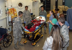 Hyperbaric Medicine Flight personnel and Aerospace Expeditionary Force personnel transport cancer patient Jeremiah Harutyunyan by gurney after he received hyperbaric oxygen treatment, Dec. 8, 2019, at David Grant USAF Medical Center, Travis Air Force Base, California. (U.S. Air Force Photo by Heide Couch)