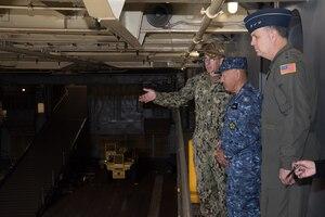 Military members tour a ship.