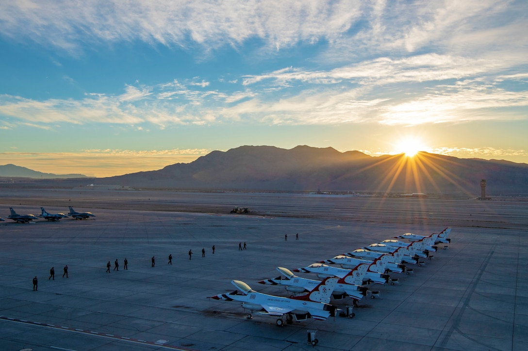 A row of aircraft is seen from the air with the sun shining over mountains in the backdrop.