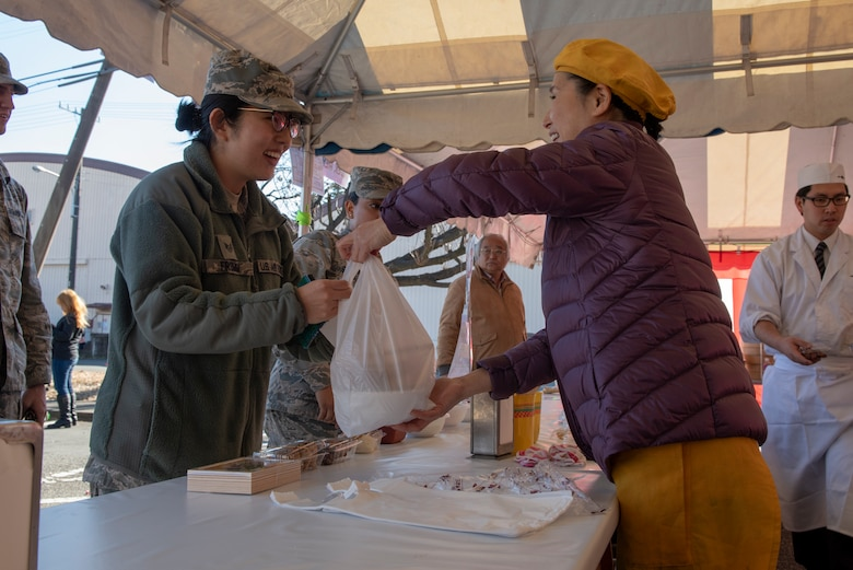 A member of the Japanese Welfare Association provides food to a member of Team Yokota at the annual Japanese Culture Day at Yokota Air Base, Japan, Jan. 11, 2019.