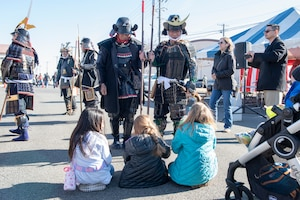 A pair of men in traditional samurai armor have a chat with a set of young girls at the annual Japanese Culture Day at Yokota Air Base, Japan, Jan. 11, 2019.