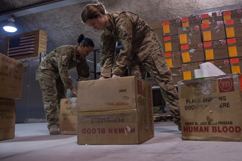 Staff Sgt. Jasmine Gates, left, and Staff Sgt. Alexis Ellingson, both 379th Expeditionary Aeromedical Evacuation Squadron aeromedical evacuation technicians, check boxes used for transporting blood for defects in the Blood Transshipment Center (BTC) Jan. 9, 2019, at Al Udeid Air Base Qatar. Ellingson and Gates volunteered time to assist Airmen at the BTC in preparing blood products for transport. The BTC is comprised of a four-person team that orchestrates the flow of blood and platelet products to 72 forward operating locations and eight mobile field surgical teams throughout U.S. Central Command's area of responsibility. (U.S. Air Force by Tech. Sgt. Christopher Hubenthal)