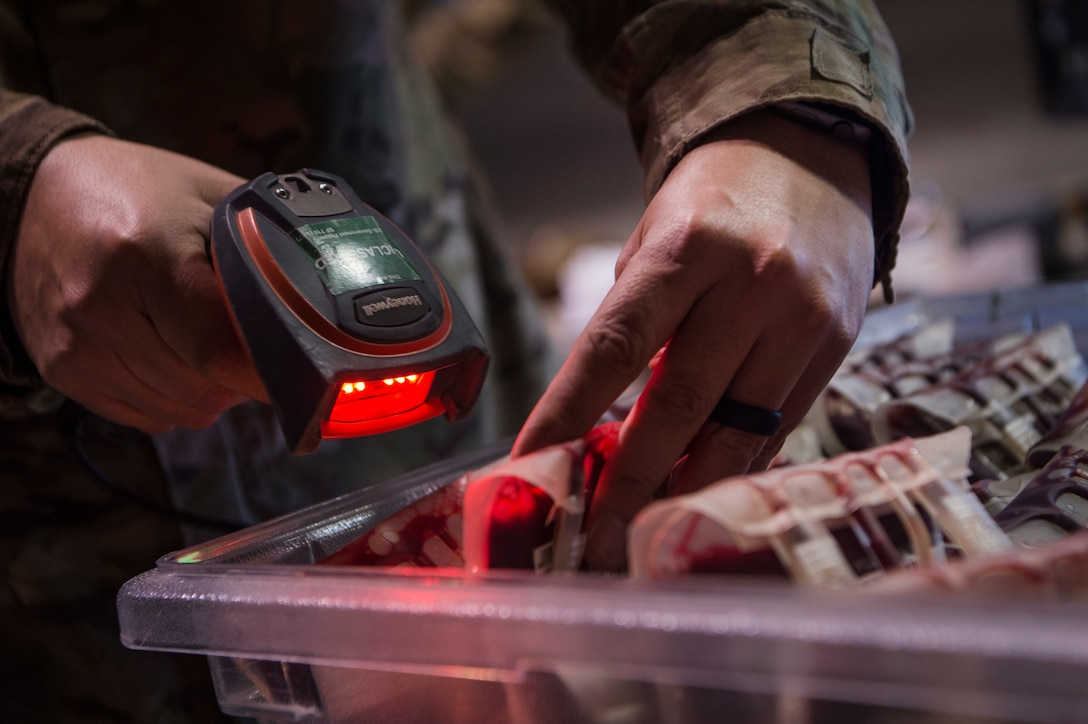 Tech. Sgt. Federico Arriaga, 379th Expeditionary Medical Group Blood Transshipment Center (BTC) logistics craftsman, scans barcodes of blood containers in the BTC Jan. 9, 2019, at Al Udeid Air Base, Qatar. The BTC is comprised of a four-person team that orchestrates the flow of blood and platelet products to 72 forward operating locations and eight mobile field surgical teams throughout U.S. Central Command's area of responsibility. (U.S. Air Force by Tech. Sgt. Christopher Hubenthal)