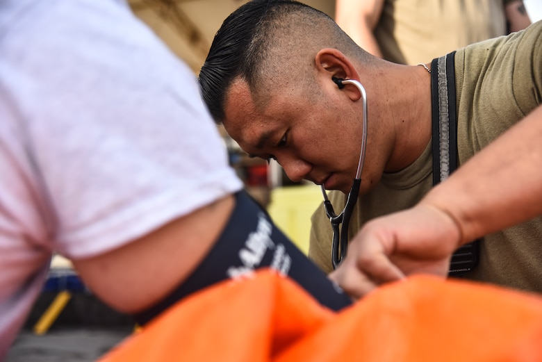 U.S. Air Force Senior Airman Peter Yoon, 380th Expeditionary Civil Engineer Squadron Fire Department firefighter, checks an Airman's vitals during a hazardous materials exercise at Al Dhafra Air Base, United Arab Emirates, Jan. 4, 2019. The 380th ECES Fire Department and Emergency Management flights conducted a joint-agency hazardous material exercise for training purposes. (U.S. Air Force photo by Senior Airman Mya M. Crosby)