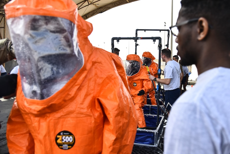 U.S. Airmen assigned to the 380th Expeditionary Civil Engineer Squadron Fire Department process through a technical decontamination during a hazardous materials exercise at Al Dhafra Air Base, United Arab Emirates, Jan. 4, 2019. The 380th ECES Fire Department and Emergency Management flights conducted a joint-agency hazardous material exercise for training purposes. (U.S. Air Force photo by Senior Airman Mya M. Crosby)