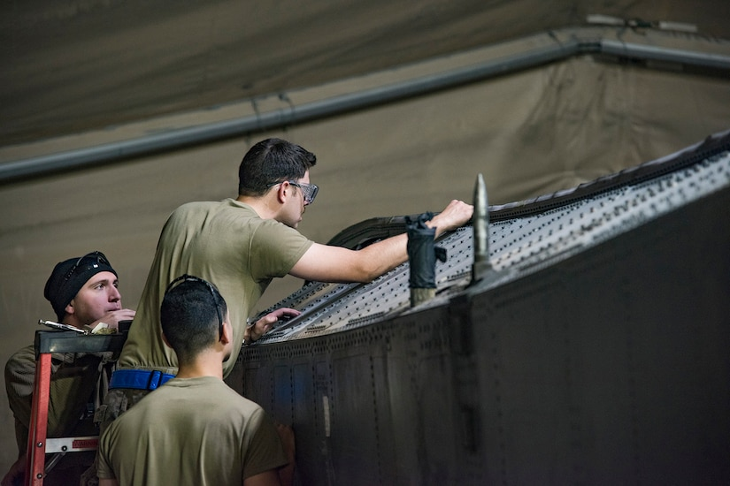 Three airmen work on a large aircraft component.