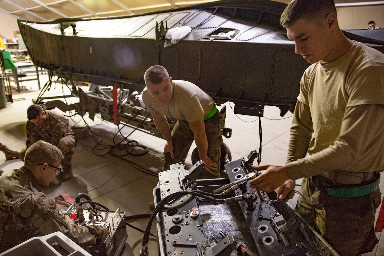 Four airmen do preventive maintenance on aircraft parts.