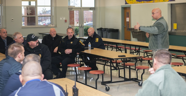 Lt. Col. Yon Dugger, 375th Security Forces Squadron commander, speaks to members of the St. Clair County Police Department and Scott Elementary School, Dec. 21, 2018, at Scott Air Force Base, Illinois. The organizations met to discuss base procedures in the event of an active shooter incident to include a walkthrough of the school to locate all possible exit points and potential safe rooms in the building.