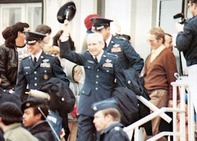 U.S. Air Force Col. Thomas E. Schaefer, ranking military officer among the former Iranian hostages, doffs his service cap to the cheering crowd as he departs the U.S. Air Force Hospital in Wiesbaden, Germany, Jan. 20, 1981. His next stop: the United States of America. (U.S. Air Force photo)