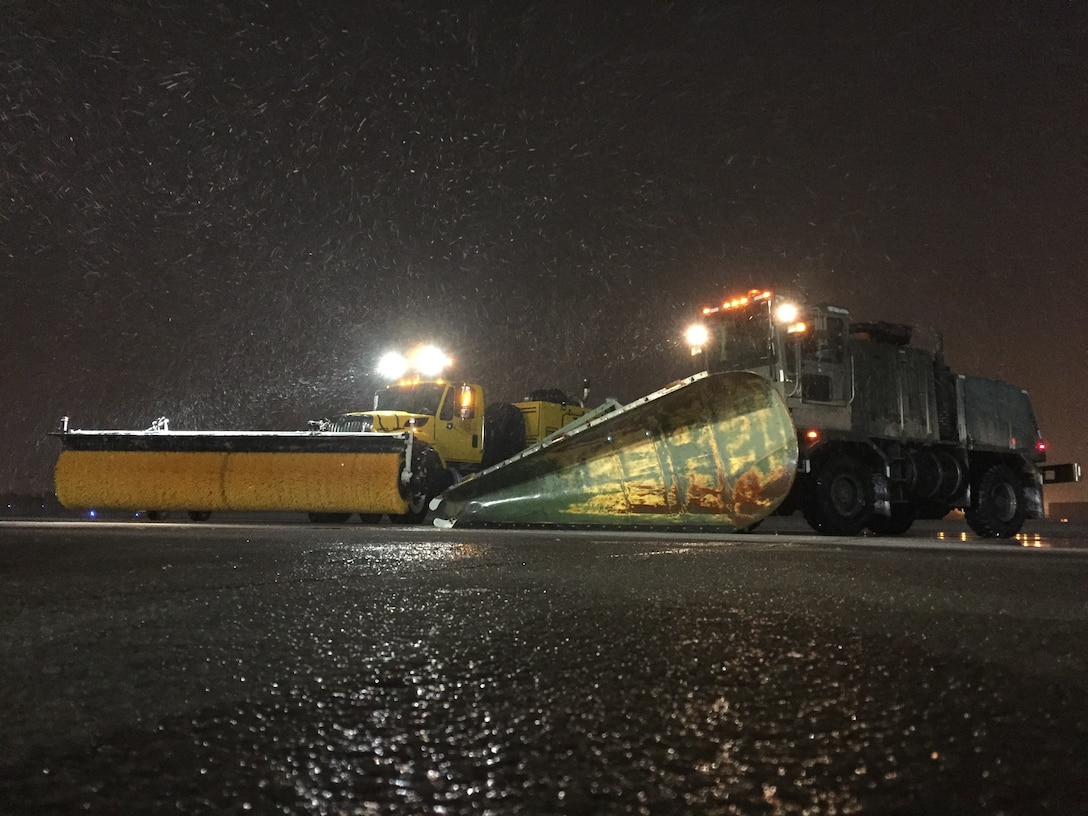 Snow removal equipment stages near the main runway just after dark as crews from the 72nd Civil Engineer Directorate prepare to sweep the runway to ensure the airfield remains open to traffic on Jan. 3, 2019. The 72nd CED has kept the runways open during the winter storm currently impacting Oklahoma. (U.S. Air Force photo/Greg L. Davis)