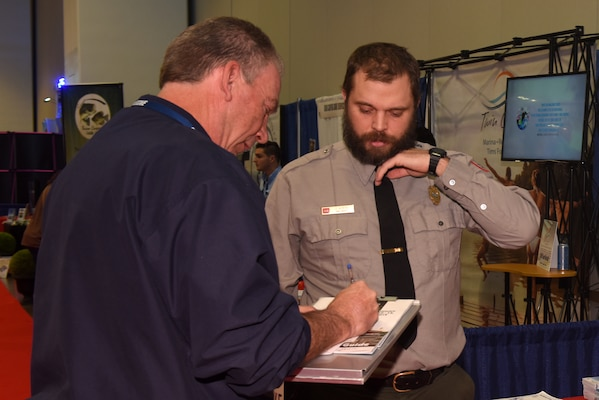 Old Hickory Lake Park Ranger Jacob Albers provides information to a visitor Jan. 10, 2019 during the Nashville Boat Show at Music City Center in Nashville, Tenn. (USACE photo by Lee Roberts)