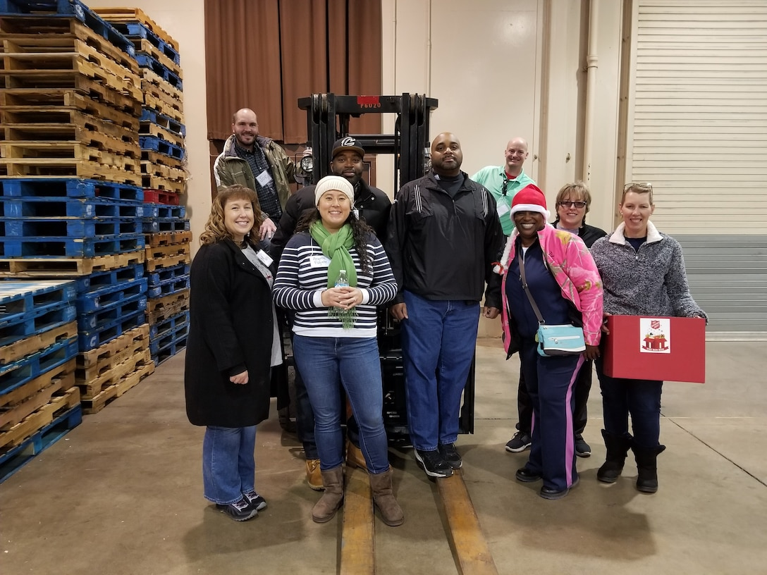 Volunteers stand around a forklift in a warehouse for a photo
