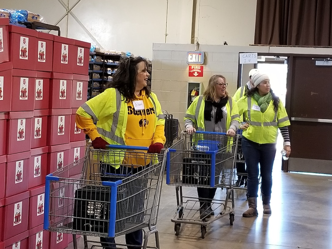Three women in yellow push carts around warehouse