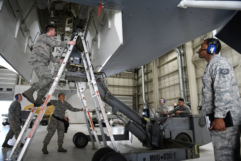 Judges for the annual weapons load competition watch as the 28th Munitions Squadron load crew install a second GBU-38 Joint Direct Attack Munition onto a simulated B-1 bomber at Ellsworth Air Force Base, S.D., Jan. 7, 2019. Participants competed to be recognized as the 28th Maintenance Group's best load crew for 2018. (U.S. Air Force photo by Airman 1st Class Christina Bennett)