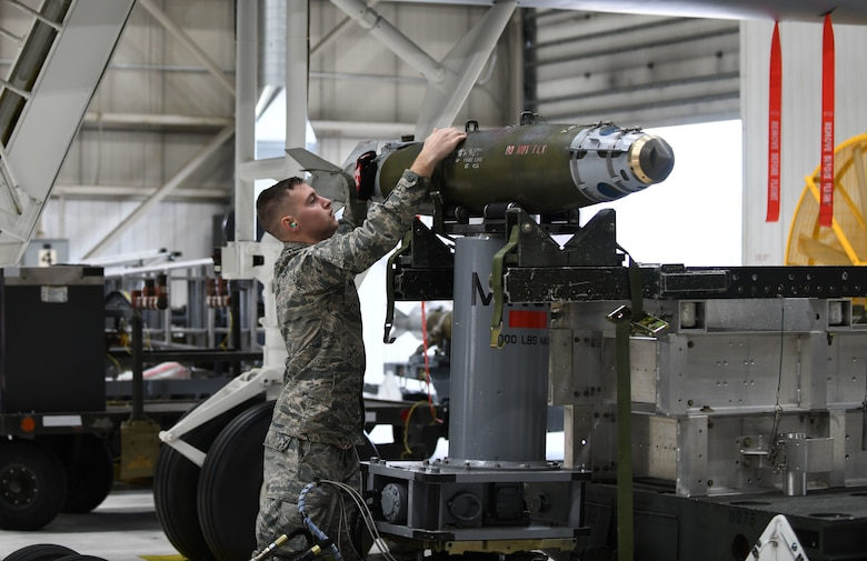 Airman 1st Class Falcon Wilson, a 34th Aircraft Maintenance Unit load crew member, inspects an inert GBU-38 Joint Direct Attack Munition for damage prior to loading it onto a simulated B-1 bomber at the annual weapons load competition at Ellsworth Air Force Base, S.D., Jan.7, 2019.  Each load crew is made up of four Airmen, with each one being responsible for a different aspect of the operation. (U.S. Air Force photo by Airman 1st Class Christina Bennett)