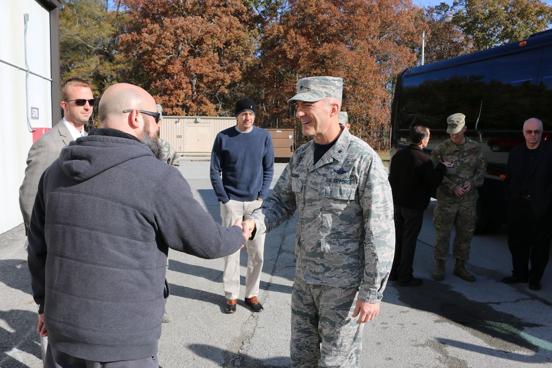 Air Force Test Center Commander Brig. Gen. Christopher Azzano, right, is greeted by Sean Smith outside of the Aerodynamic & Propulsion Test Unit during Azzano's Nov. 16 tour of Arnold Air Force Base. Azzano and other AFTC leadership recently visited Arnold to take part in the AFTC Strategic Offsite. The Offsite was Azzano's first since assuming the post of AFTC commander. (U.S. Air Force photo by Bradley Hicks) (This image was altered by obscuring badges for security purposes)