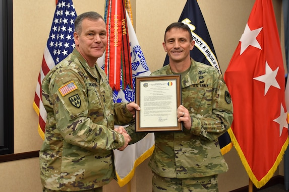 Col. Timothy G. Dalton receives his charter as the incoming U.S. Army Training and Doctrine Command Capabilities Manager for Space and High Altitude, from Lt. Gen. James H. Dickinson, commanding general, U.S. Army Space and Missile Defense Command/Army Forces Strategic Command, during a Jan. 4, 2019, Change of Charter at the command's headquarters on Redstone Arsenal, Alabama. The TCM SHA belongs to SMDC's Future Warfare Center but receives operational authority through TRADOC's four-star general. (U.S. Army photo by Ronald Bailey)