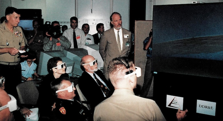 Viewing one of the 3-D displays during JWID97 execution is General Malchase D. Shalikashvili, Chairman of the Joint Chiefs of Staff and General John J. Sheehan, Supreme Allied Command Atlantic, NATO, 1997. 