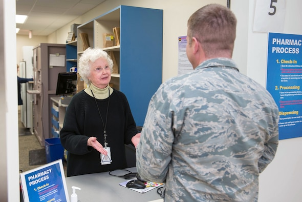 A 55th Medical Group Red Cross volunteer, speaks to a serivce member in the Ehrling Burquist pharmacy Jan. 7, 2019, Offutt Air Force Base, Nebraska. The base pharmacy carefully screens all medications to ensure quality controlled products are correctly supplied to their patients. (U.S. Air Force photo by Zachary Hada)