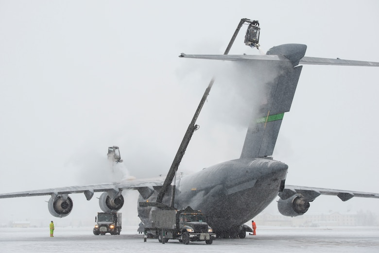 Airmen assigned to the 732nd Air Mobility Squadron de-ice a C-17 Globemaster III