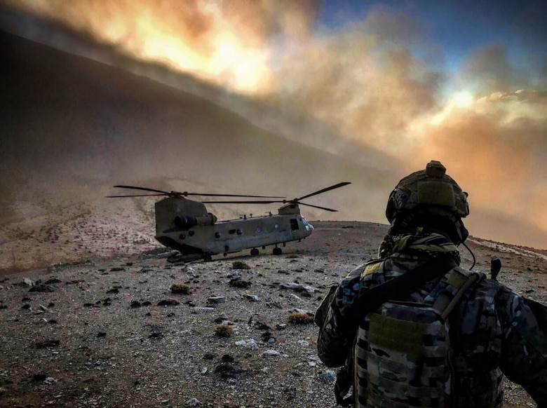 An 83rd Expeditionary Rescue Squadron Airman observes a U.S. Army CH-47 Chinook