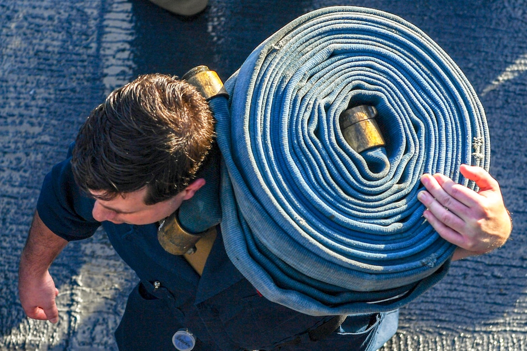 A sailor carries a coiled hose on his shoulder