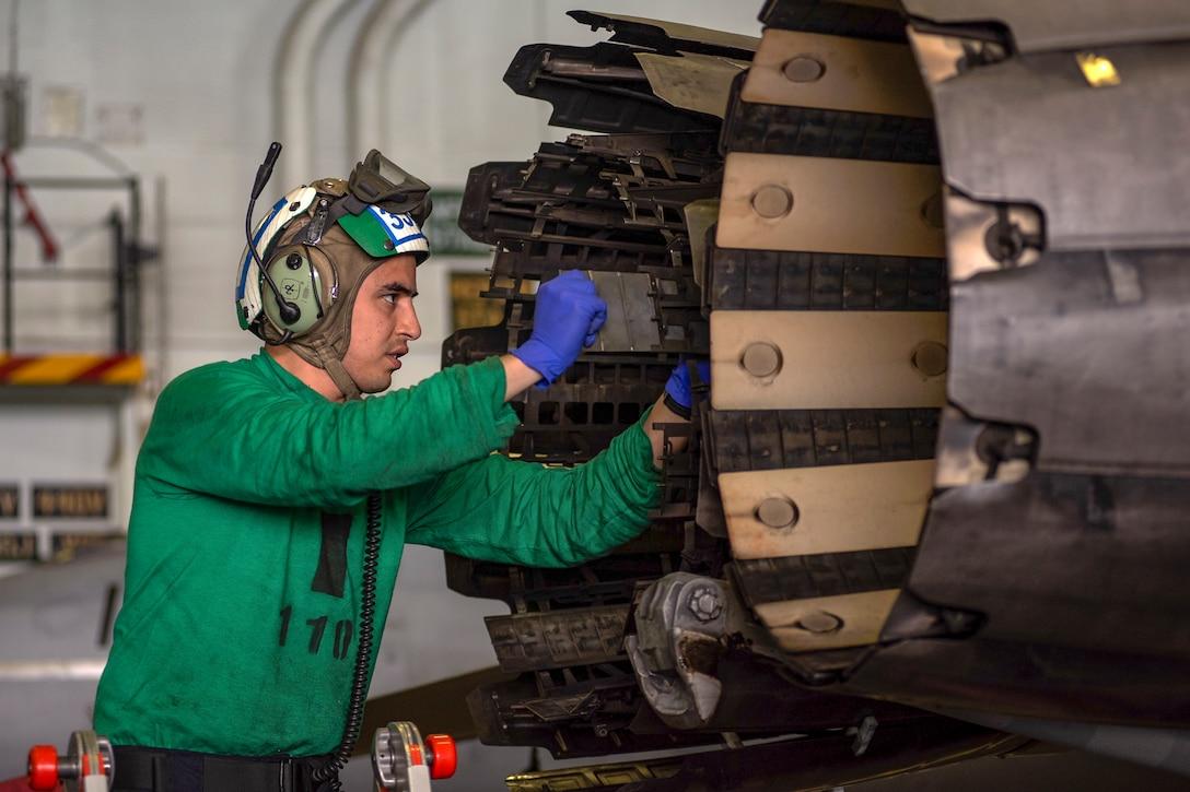 A sailor works on a Super Hornet's exhaust nozzle.