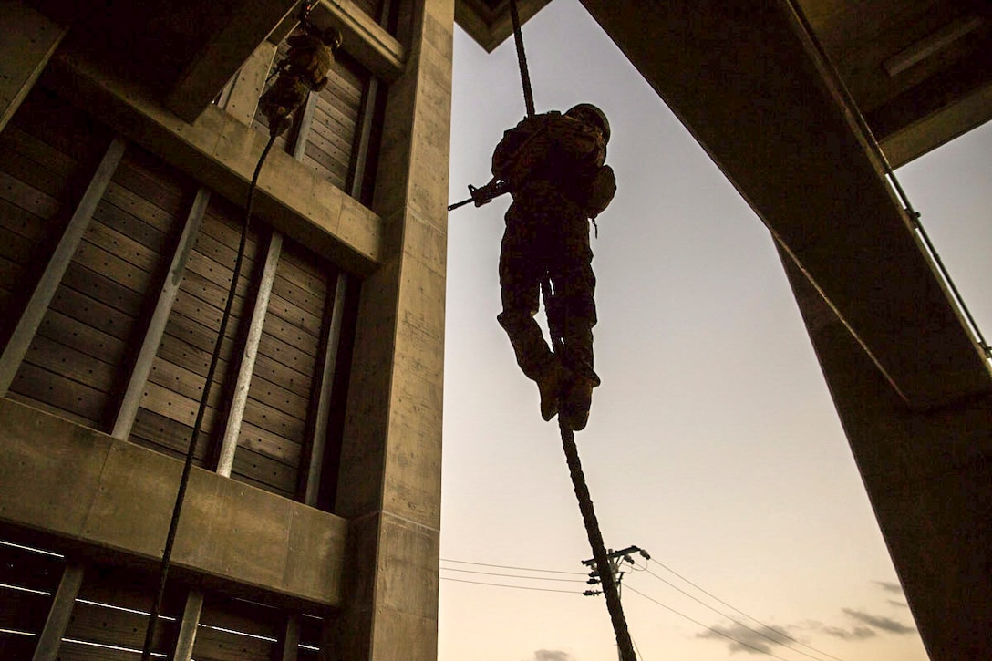 Marines descend down ropes hung from wooden platforms outside.