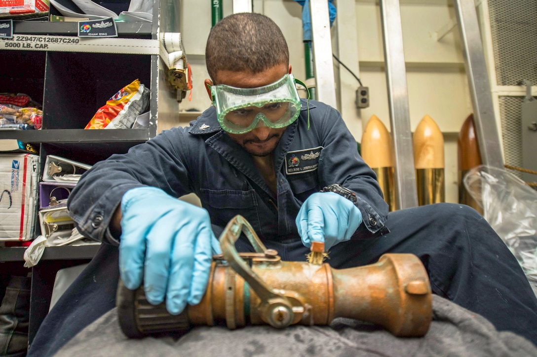 A sailor conduct maintenance on pipes.