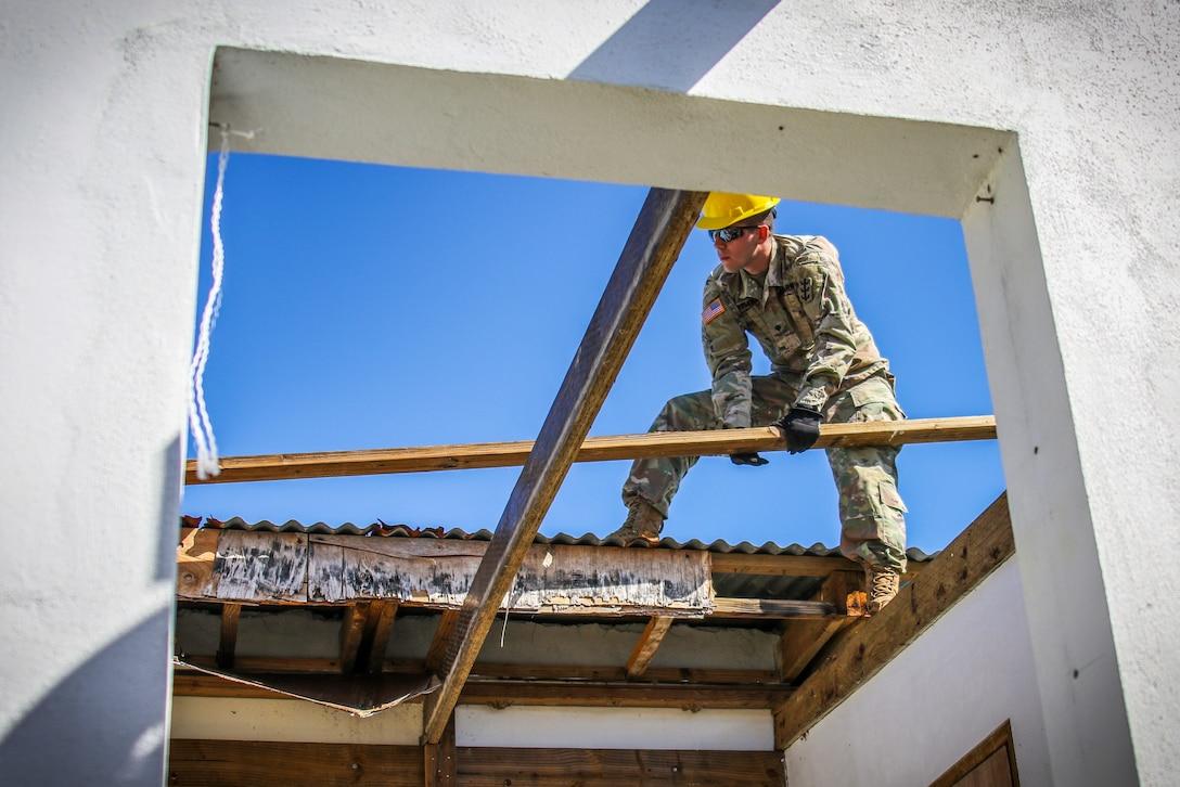 A soldier surveys a damaged roof.