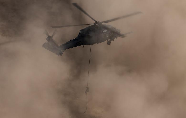 A pararescueman rappels out of an HH-60G Pave Hawk