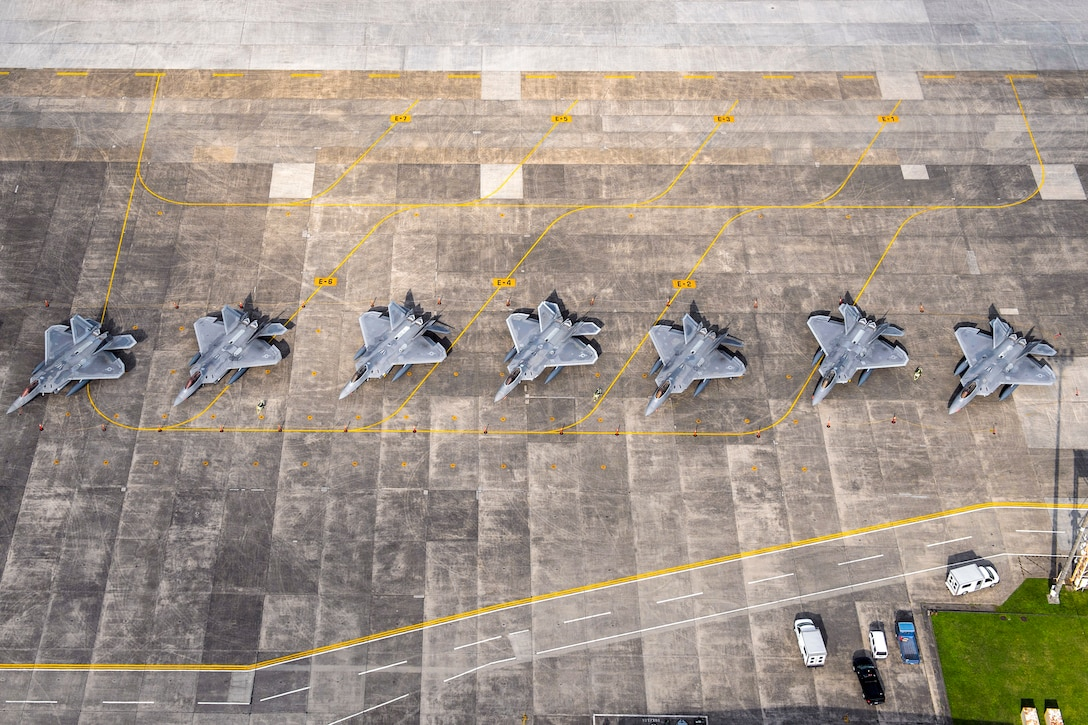 Eight U.S. Air Force F-22 Raptors sit on the flightline